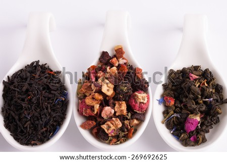 Dry tea in white bowls, on white background. Leaves of red, green and black tea. Macro photo. - stock photo
