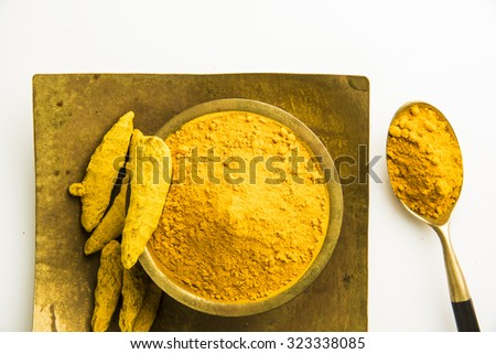 dry Turmeric and turmeric powder in square brass plate and brass bowl and a brass spoon, horizontal and top view - stock photo