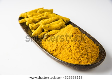 dry Turmeric and turmeric powder in wooden plate over white background , horizontal and front view - stock photo