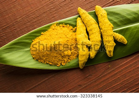 dry Turmeric and turmeric powder over green leaf on wooden background, horizontal and top view - stock photo