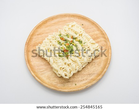 Dry vegetables topping on Instant noodles served on wood dish - stock photo