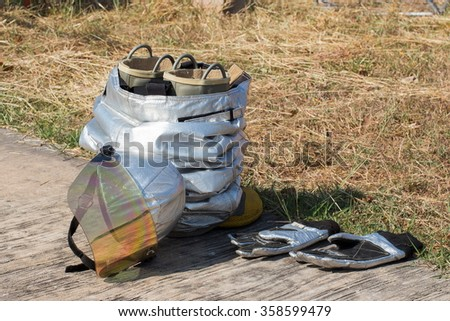 Dry with sun after Cleaning Firefighter uniform and yellow  helmet - stock photo
