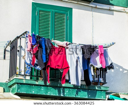 Drying clothes hanging on the balcony of the old building - stock photo