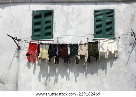 Drying clothes hanging outside the window of an old building facade - stock photo