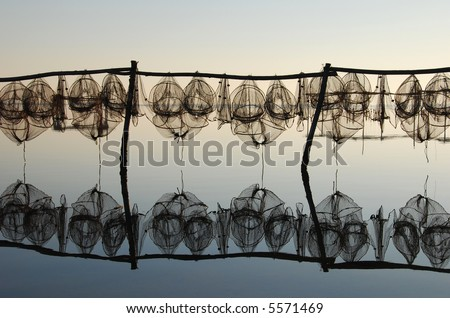 drying fish trap nets - amazing light and reflection on the calm ocean