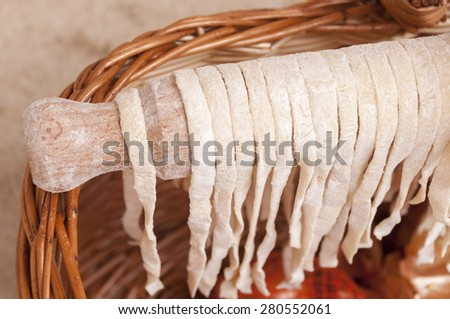 Drying homemade pasta on the wooden roller - stock photo