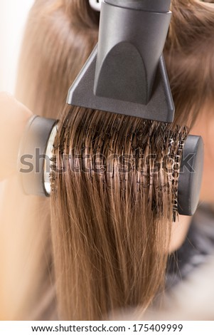 Drying long brown hair with hair dryer and round brush. Close-up. - stock photo