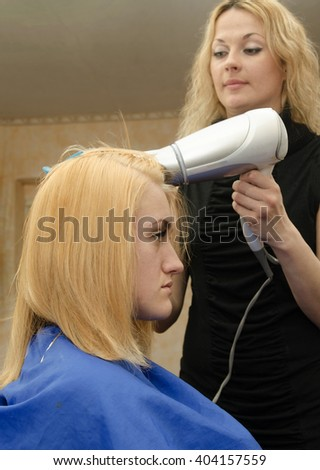 drying of ginger  painted  hair with the hairdryer - stock photo