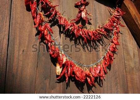 Drying Paprikas red chili peppers at the wooden background - stock photo