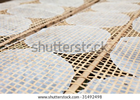 Drying Vietnamese Rice Paper Under Sun in Mekong Delta - stock photo