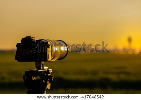 DSLR camera is standing outside to make pictures from a nice sunrise. - stock photo