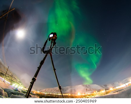 DSLR Camera on tripod shooting amazing green aurora borealis (northern lights) in moonlit night - stock photo