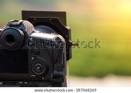 DSLR camera with gradient filter focus on sunrise landscape view. - stock photo