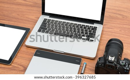 DSLR digital camera with tablet and notebook laptop on wooden desk table