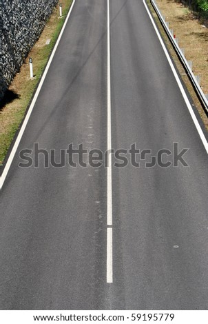 dual carriageway with white stripes and black asphalt - stock photo