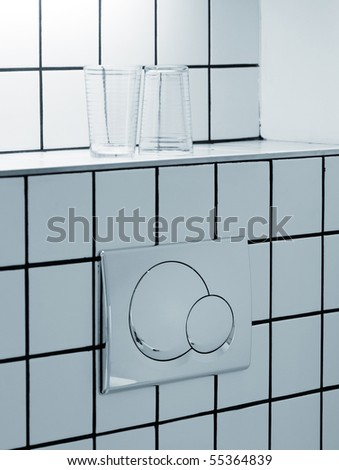 Dual flush toilet button and drinking glasses - stock photo