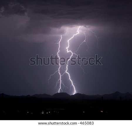 Dual lightning strikes over the Roskruge Mountains in the desert southwest of the United States - stock photo