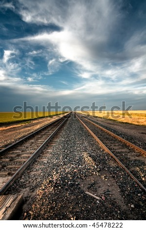 Dual train tracks through farmland with dramatic blue sky