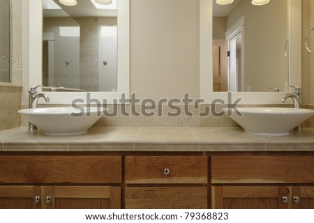 Dual vessel porcelain sinks are set on a wooden vanity with a tiled counter. There are mirrors set above each sink. Horizontal shot. - stock photo