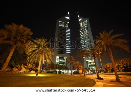 DUBAI - APRIL 18: Emirates Towers and area with palms at night time, 18 april 2010 in Dubai, UAE. Jumeirah Emirates Towers, Dubai's finest city hotel, is located  in commercial business district. - stock photo