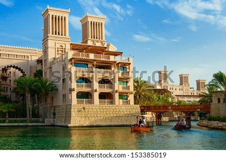 DUBAI - JUNE 3: The famous hotel and tourist district of Madinat Jumeirah 3, 2013 in Dubai. Built with ancient style, has many shops, restaurants and viewing platforms on Burzh al Arab - stock photo