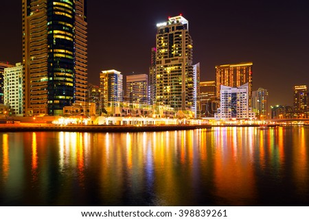 Dubai marina illuminated in night, United Arab Emirates - panorama of skyscrapers