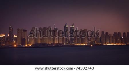 Dubai Marina in the night. Panoramic view from gulf - stock photo