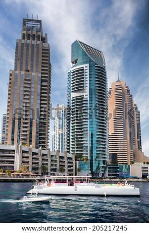 Dubai Marina with boat against skyscrapers in Dubai, United Arab Emirates - stock photo
