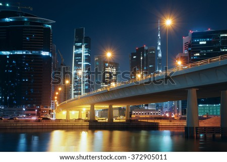 Dubai nighttime skyline with modern buildings, street lights and a bridge. Downtown Dubai, UAE.  - stock photo