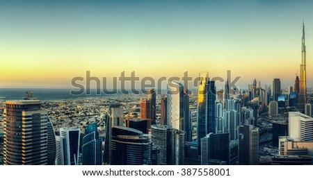 Dubai's business bay with many modern skyscrapers. Beautiful aerial cityscape by colorful sunset.