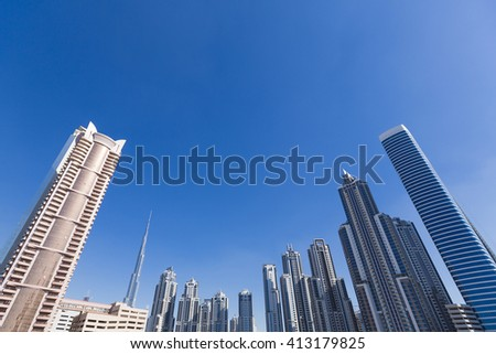 Dubai skyline with residential skyscrapers and Burj Khalifa the tallest building over the horizon in the background. - stock photo
