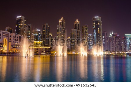 Dubai skyscrapers and dancing fountain in the evening