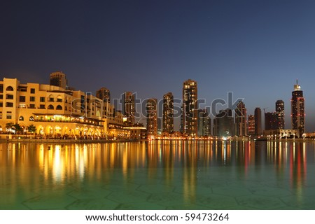 Dubai skyscrapers and other buildings at night time, view from water