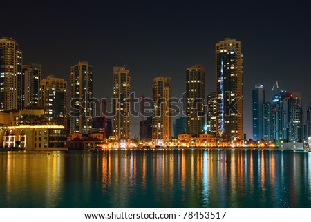 Dubai skyscrapers and other buildings at night time, view from water. UAE