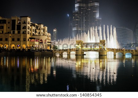 DUBAI, UAE. - APRIL 29 : Dubai fountain show on April 29, 2013 in Dubai, UAE. The Dubai Fountain is the worlds largest choreographed fountain system set on the 30-acre manmade Burj Khalifa Lake. - stock photo