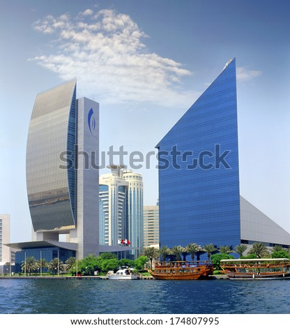 DUBAI, UAE - AUGUST 15: Modern architecture on the banks Dubai Creek on August 15, 2004. The creek is dividing the city into two main sections Deira and Bur Dubai and stands are many great buildings - stock photo