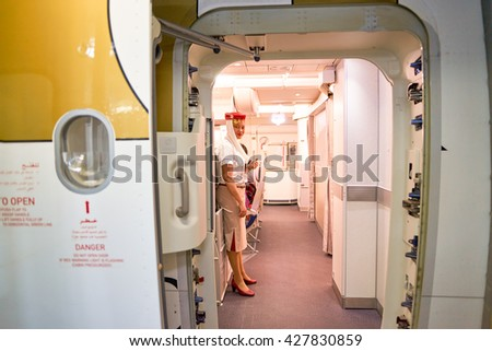 DUBAI, UAE - CIRCA APRIL, 2016: Emirates crew member meet passengers on board of Boeing 777. Emirates is one of two flag carriers of the UAE along with Etihad Airways and is based in Dubai. - stock photo