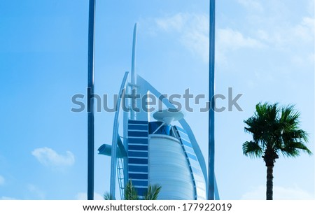 """DUBAI, UAE - DECEMBER 10, 2013: A general view of the world's first seven stars luxury hotel Burj Al Arab """"Tower of the Arabs"""", also known as """"Arab Sail"""",  reflected in glass window - stock photo"""