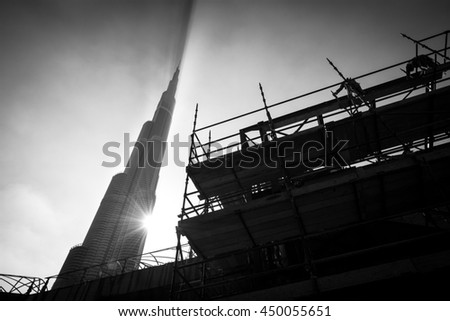 DUBAI, UAE - DECEMBER 8: Black and white Burj Khalifa with sun flare and building works in foreground. The highest structure in the world: 829, 8 m., 163 floors. December 8, 2012, Dubai, UAE, Asia.
