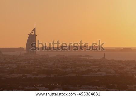DUBAI, UAE - December 25 2013 Burj Al Arab the luxury 7 stars hotel and jumeirah beach in panoramic orange silhouette sunset  - stock photo