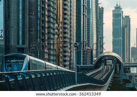 DUBAI, UAE - DECEMBER 16, 2015: Dubai downtown architecture in the evening with a metro monorail train arriving at the station. - stock photo