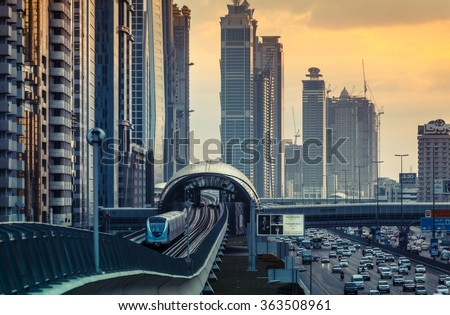DUBAI, UAE - DECEMBER 16, 2015: Dubai's downtown architecture in the evening with metro monorail train arriving at the station. - stock photo