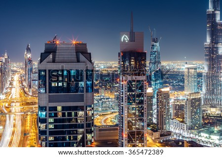 DUBAI, UAE - DECEMBER 09, 2015: Scenic aerial view of Dubai's business bay architecture by night with residential buildings and Sheikh Zayed road. - stock photo