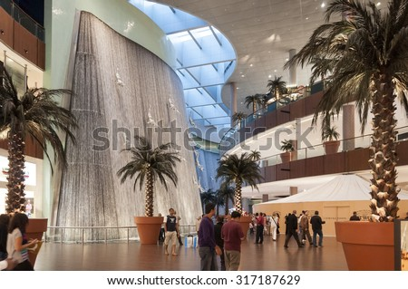 Dubai, UAE - February 23, 2012: Modern silver colored male sculpture installed to create a jumping effect on the fountain, inside the Dubai Mall, the largest shopping mall of the world. - stock photo
