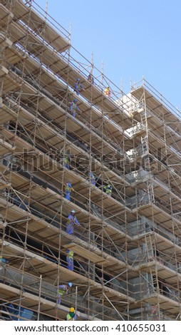 Dubai, UAE FEBRUARY 10, 2016: Scaffolding erected to support building form work and also function as the platform for construction workers standing high level at the construction site - stock photo
