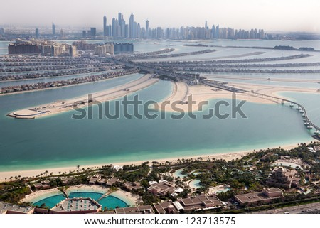 DUBAI, UAE - JANUARY 20: Jumeirah Palm island  on January 20, 2011 in Dubai, UAE. Jumeirah Palm is artificial and unique island in Dubai with skyscrappers on the background - stock photo