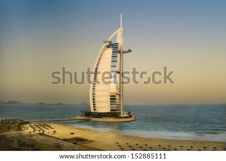 DUBAI, UAE - JANUARY 04: The world's first seven stars luxury hotel Burj Al Arab hotel on Jan 04, 2012 in Dubai. On the background - Palm Jumeirah island and hotel Atlantis. Sunrise View - stock photo