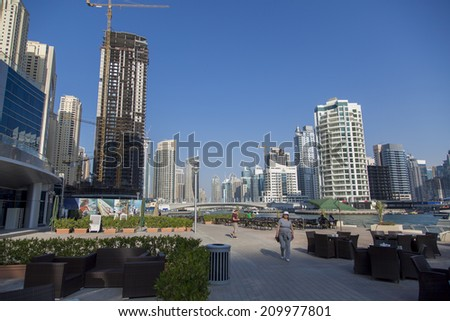 DUBAI, UAE - JANUARY 16, 2014: Unidentified people in Dubai Marina in Dubai, UAE. When the entire development is complete, it will accommodate more than 120,000 people.