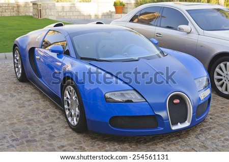 Dubai, UAE - January 08, 2012: View of a Bugatti Veyron supercar in front of Al Qasr Hotel. Veyron was named Car of the Decade and best car award (2000-??2009) by the BBC television program Top Gear.  - stock photo