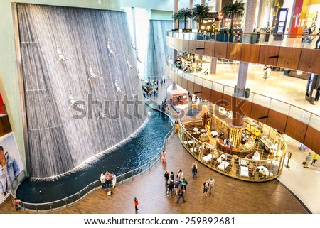 DUBAI, UAE - JANUARY 10, 2015: wide view of artistic waterfalls in Dubai Mall, the world's largest shopping mall, part of the 20 billion dollars Downtown Dubai Complex, and includes around 1,200 shops - stock photo